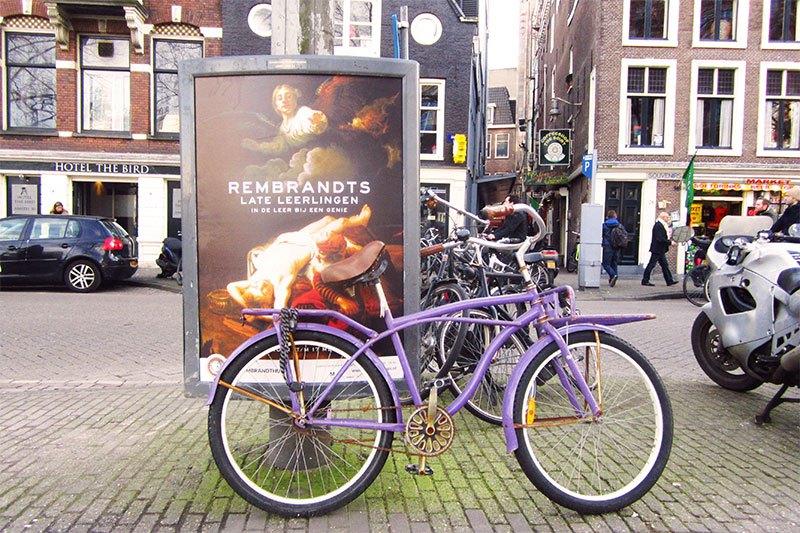 Amsterdam Lila Fahrrad lehnt an einem Plakat für Rembrandt Ausstellung