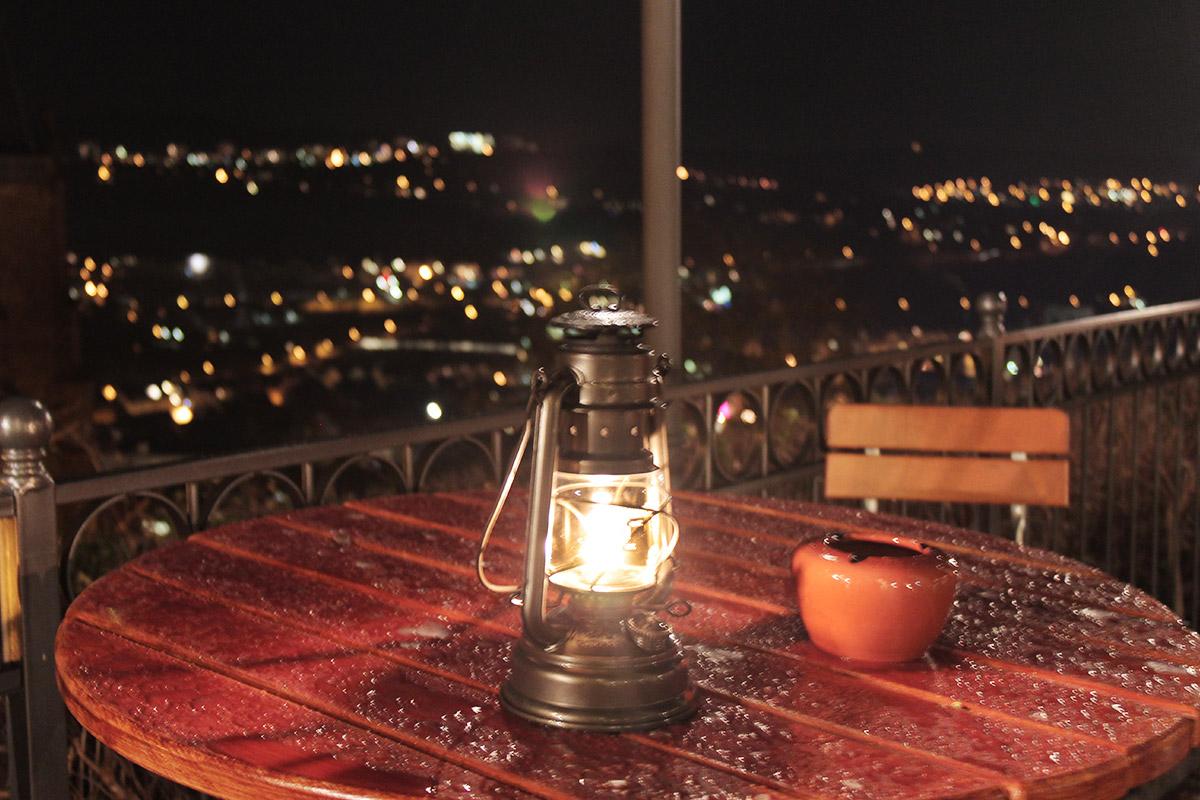 Stilleben aus Petroleumlampe und Aschenbecher dahinter das nächtliche Marburg