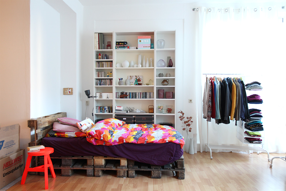Bedroom with pallet bed, Tom Dixon stool and Ikea Billy shelves