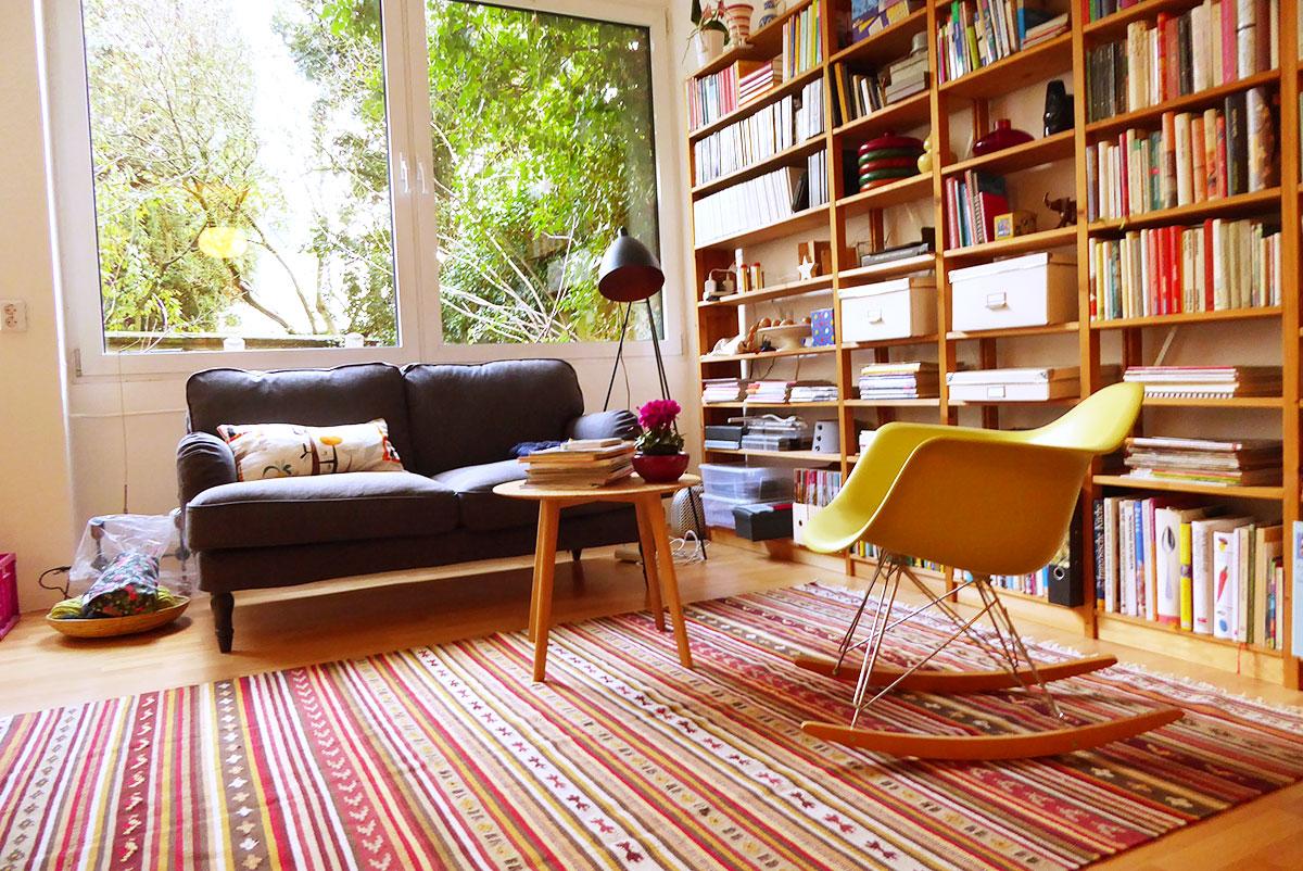 Wohnzimmer mit Lundia-Bücherregal Eames Rocking Chair, IKEA Stocksund Sofa und Kattrup Teppich