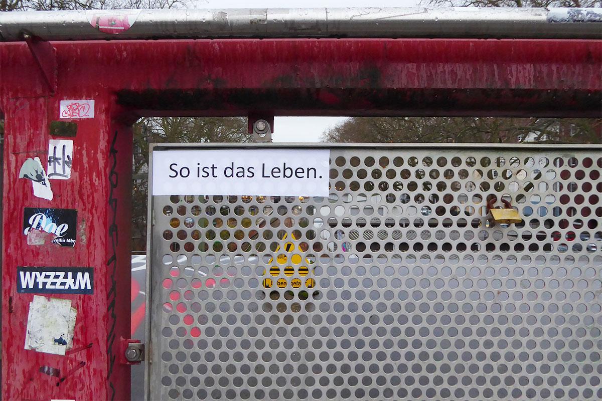 Ein Aufkleber an einem Zaun: So ist das Leben.