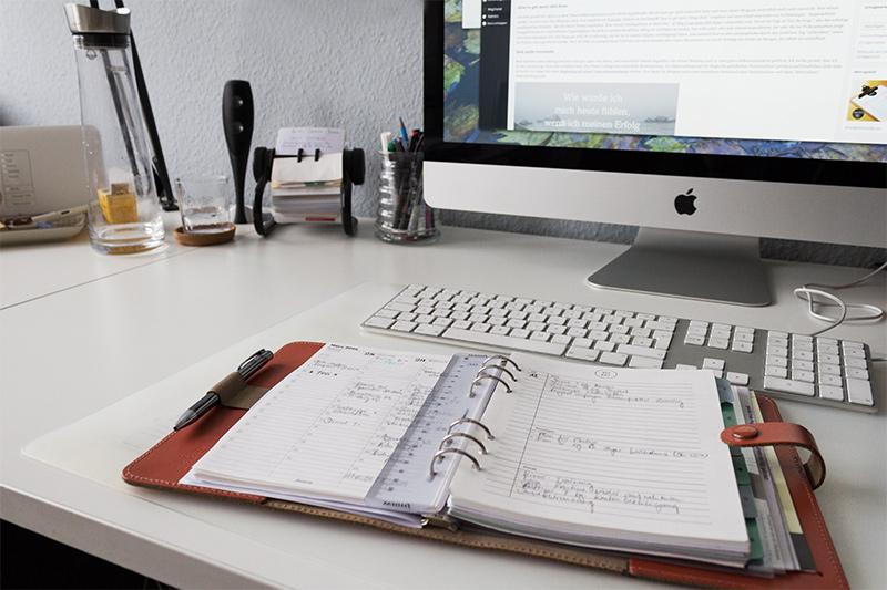 Aufgeschlagener TimePlaner auf einem Schreibtisch dahinter eine Tastatur und ein Bildschirm