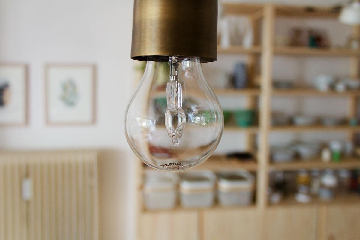 Detail Glühbirne mit LED vor einem offenen Regal