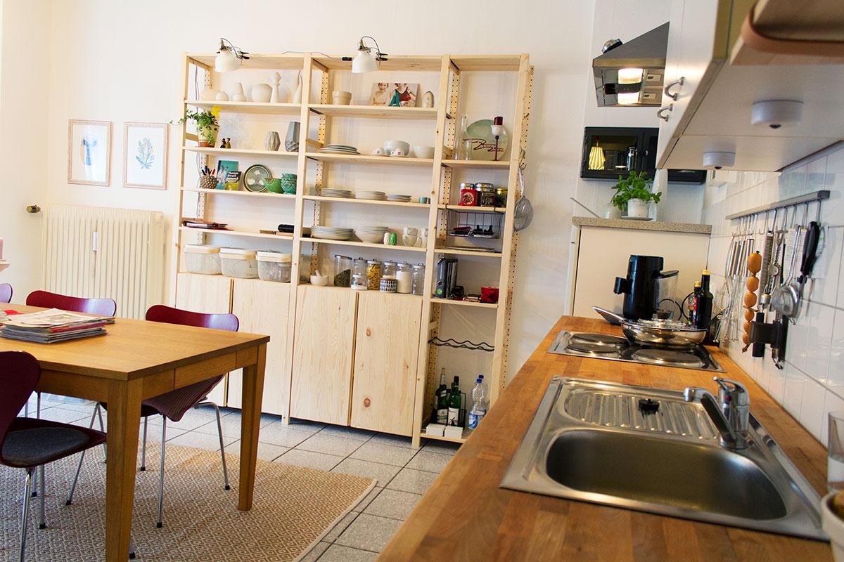Ansicht Küche mit Spülbecken im Vordergrund Regal mit Geschirr im Hintergrund