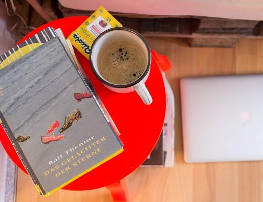 Kaffetasse, Hustenbonbons, Buch auf einem Stuhl darunter ein Laptop