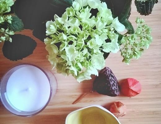 Ein Stillleben auf einem Couchtisch aus einer Hortensie, Kerze, Schale und verschiedenen Fruchtständen
