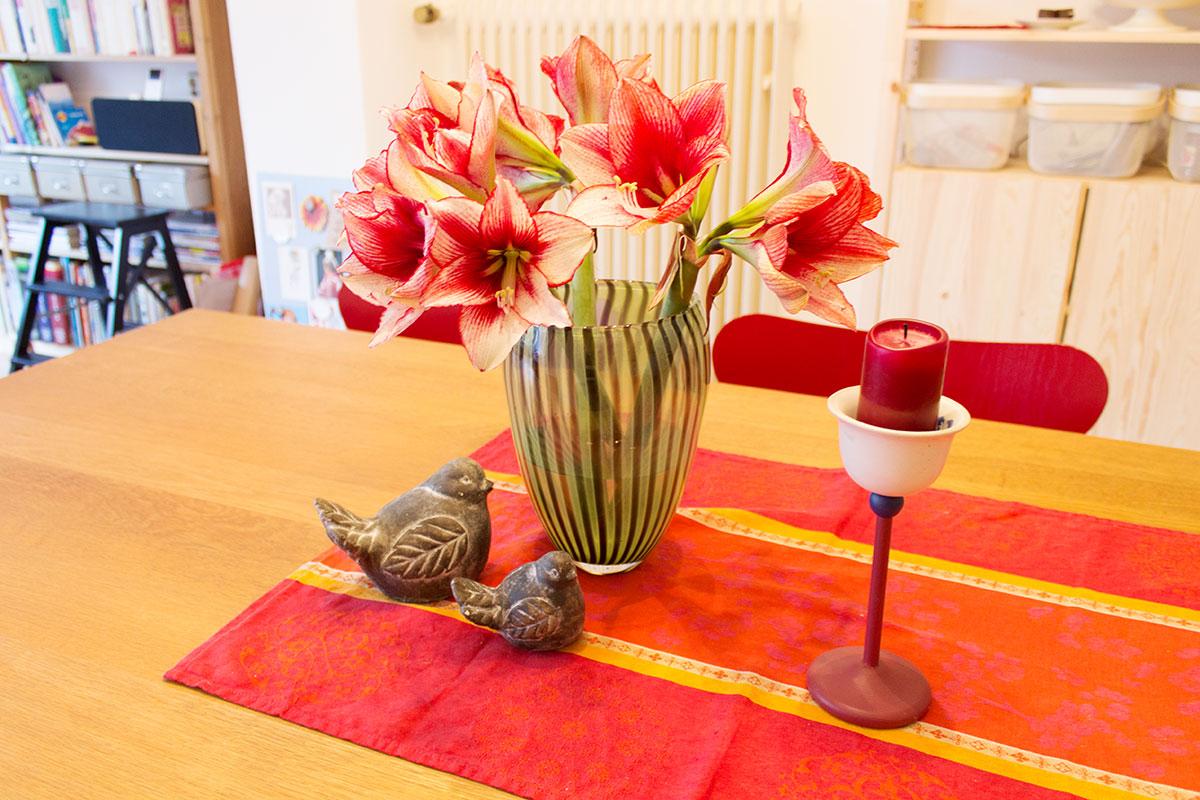 Blumenstrauß aus roter Amaryllis in grüner Vase auf einem Tisch