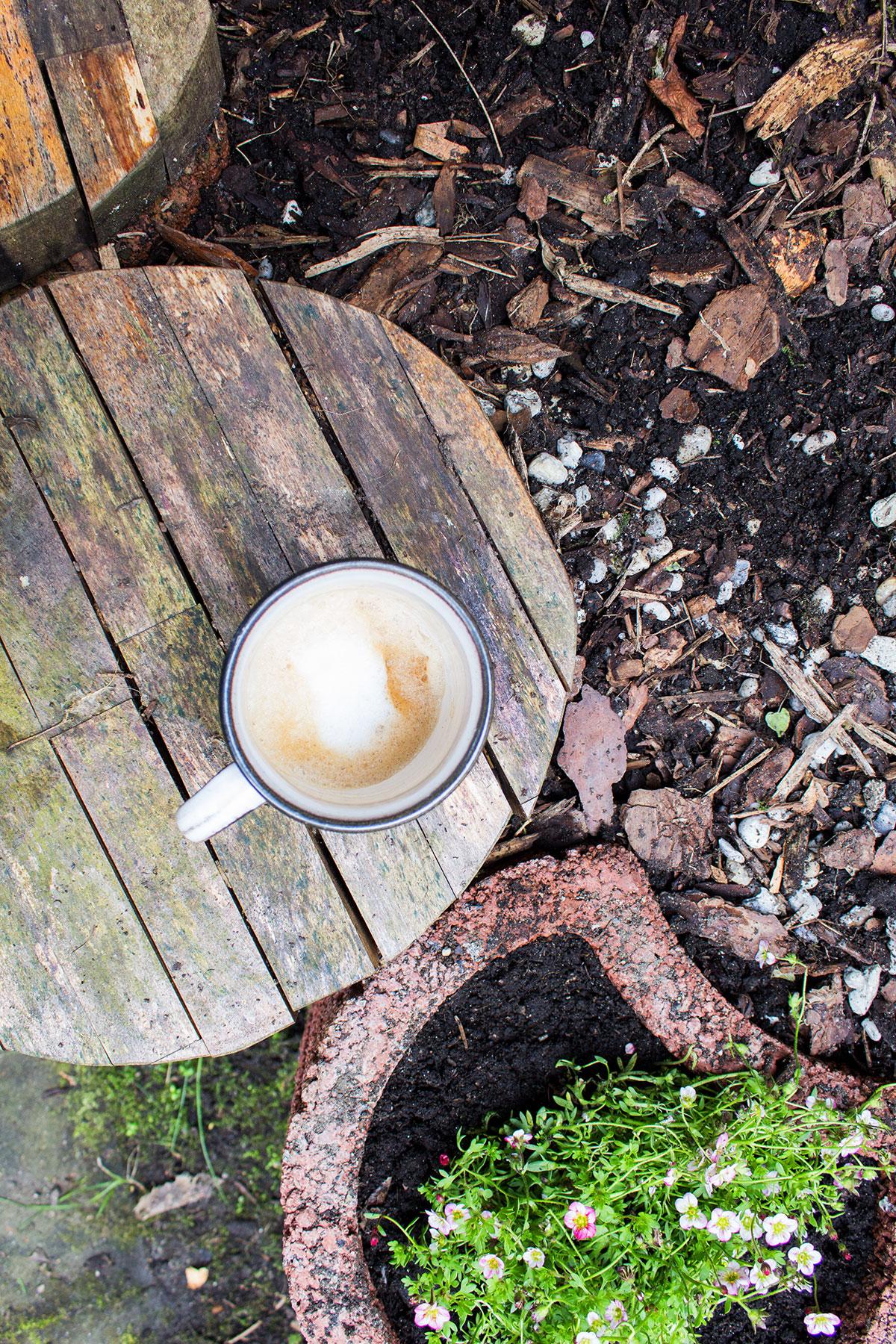 Hölzerne Bank mit Kaffetasse darauf in einem Garten