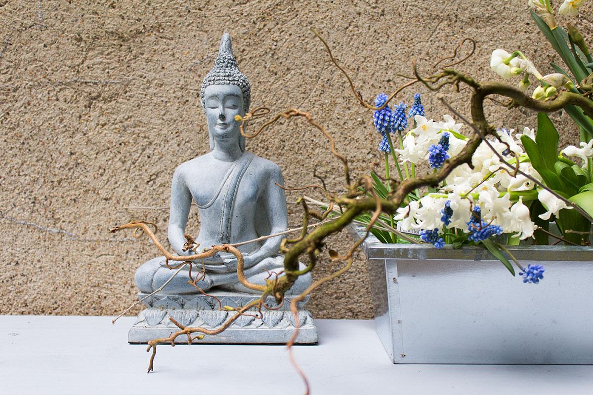 Eine Buddhafigur auf einem Gartentisch daneben Frühlingsblumen