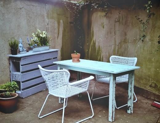 Ein Garten mit Tisch, zwei Stühlen, Konsoltisch und Blumentöpfen