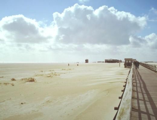 Am Strand von St. Peter-Ording im Hintergrund Pfahlbauten