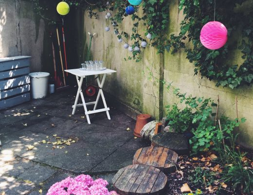 Ausschnitt aus einem Garten, Hortensie im Vordergrund, Klapptisch mit Gläsern und bunte Lampions im Hintergrund
