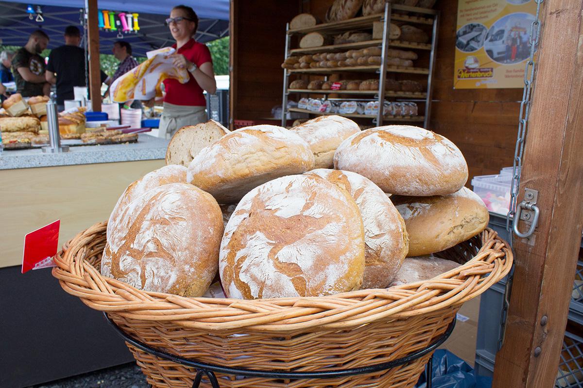 Brote in einem großen Korb dahinter eine Dame, die Brot verkauft