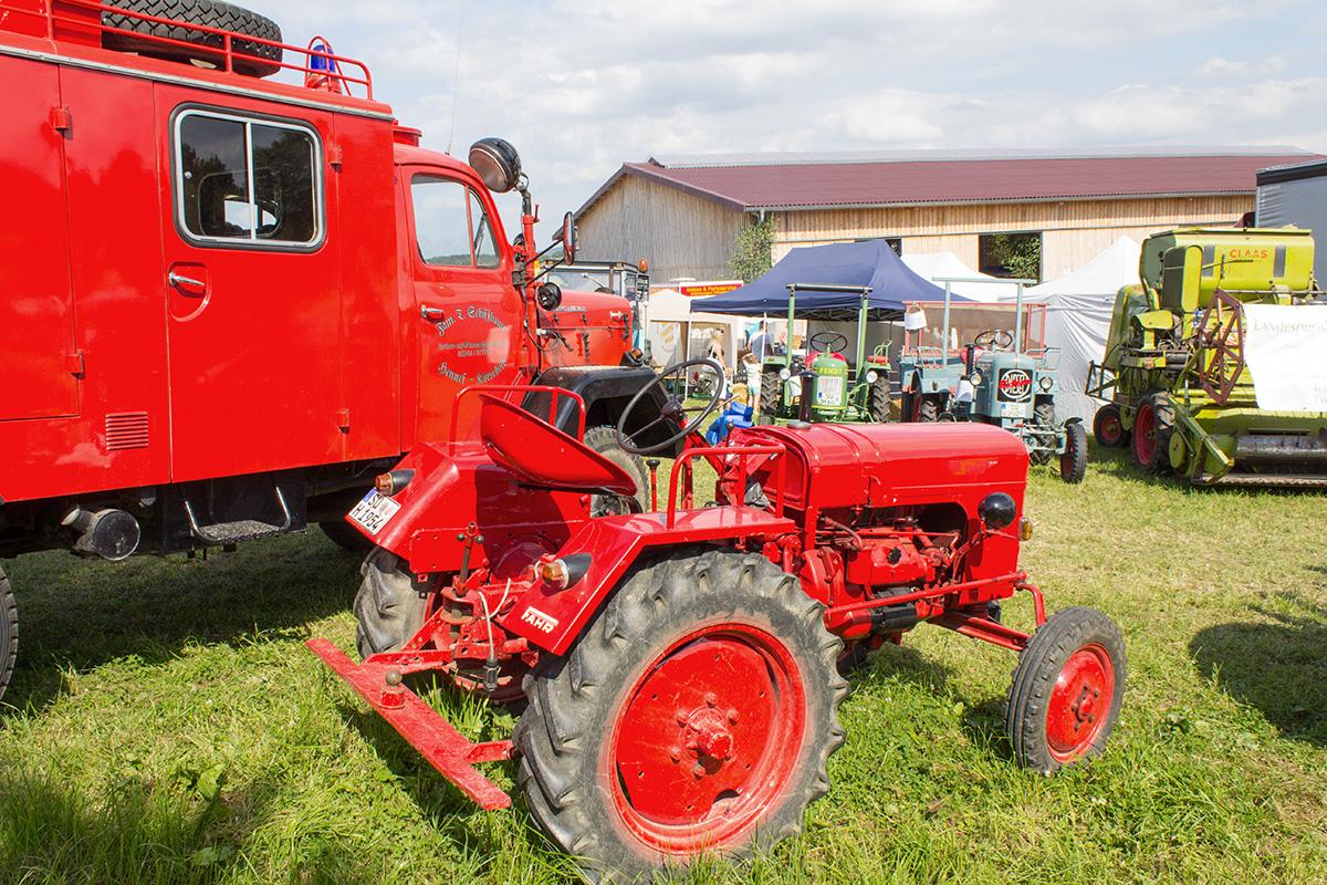 Ein alter roter Schlepper nebem einem alten Feuerwehrwagen