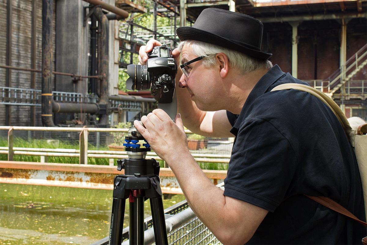 Dirk Friedrich steht hinter einem Stativ und stellt seine Kamera ein