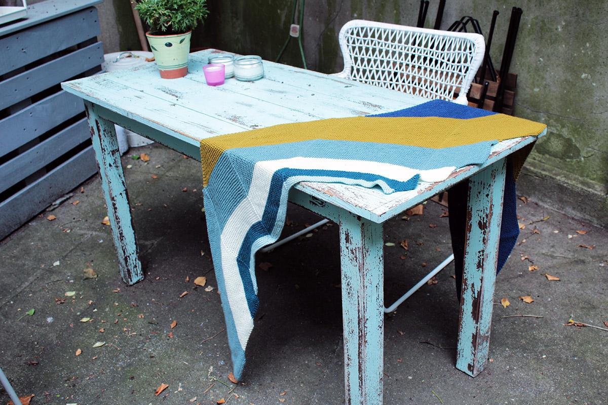 Ein selbstgestricktes Schultertuch in verschiedenen Farben liegt ausgebreitet auf einem Holztisch