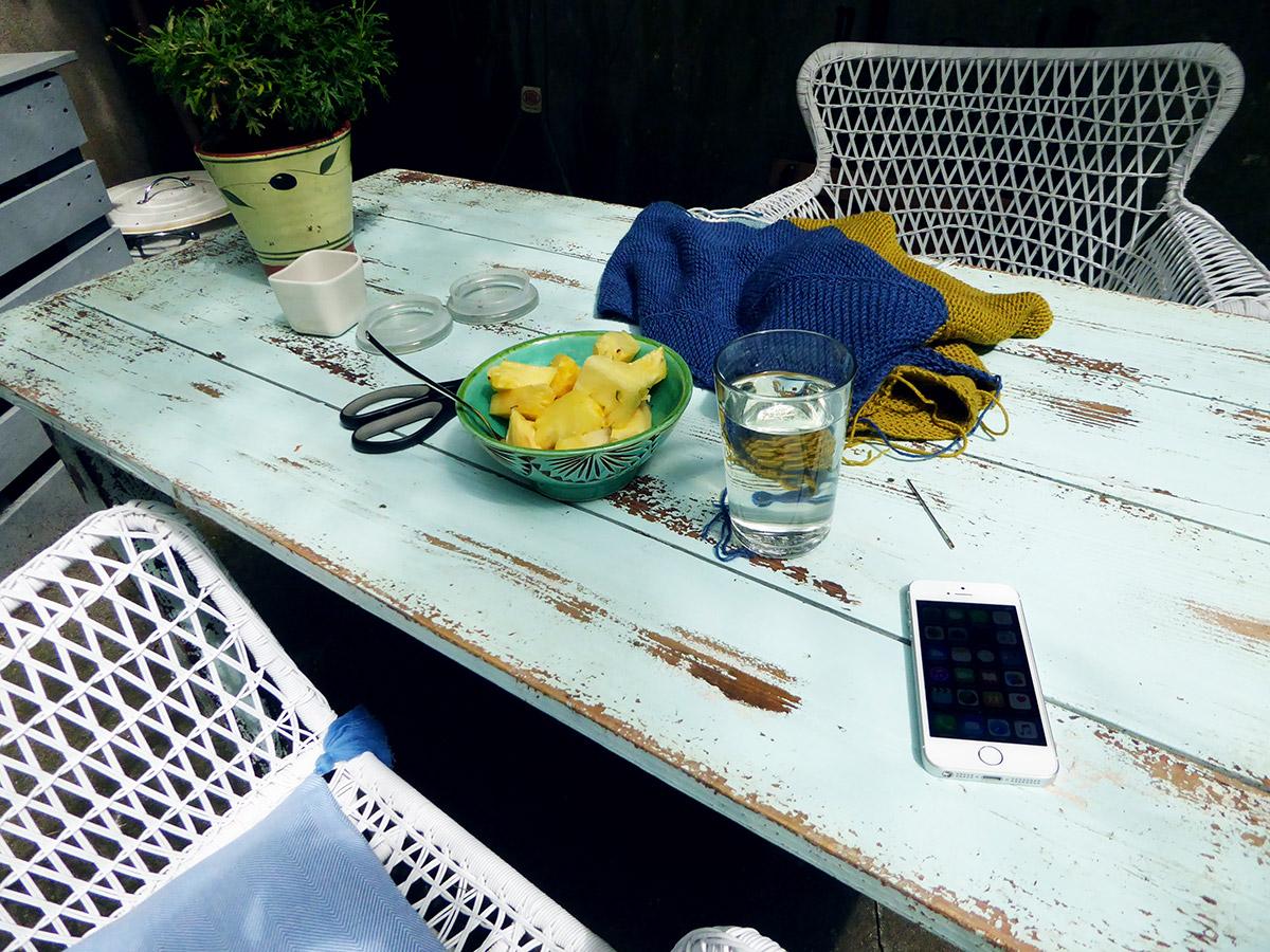 Ein türkisfarbener Holztisch darauf eine Schale mit Ananas, ein Glas Wasser, eine Schere, eine Handarbeit, ein iPhone