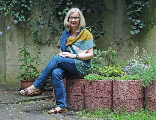 Eine Frau sitzt auf einer Gartenmauer und trägt ein selbstgestricktes Schultertuch aus Wolle