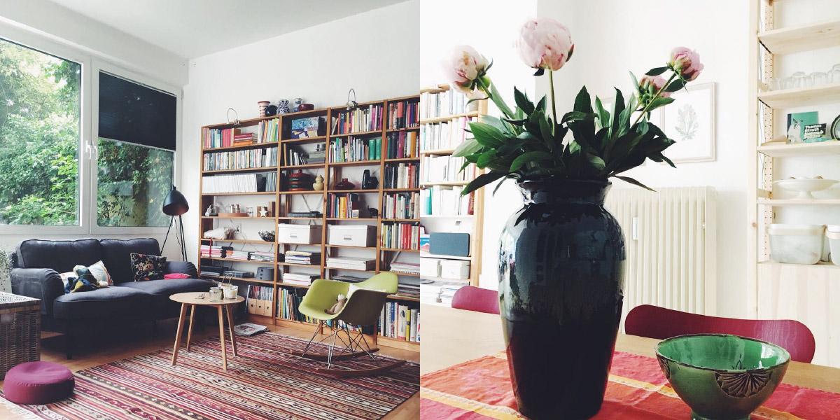 Ein Wohnraum in einem Apartment, im Hintergrund ein Bücherregal, Pfingstrosen stehen in einer hohen, dunklen Vase auf einem Esstisch
