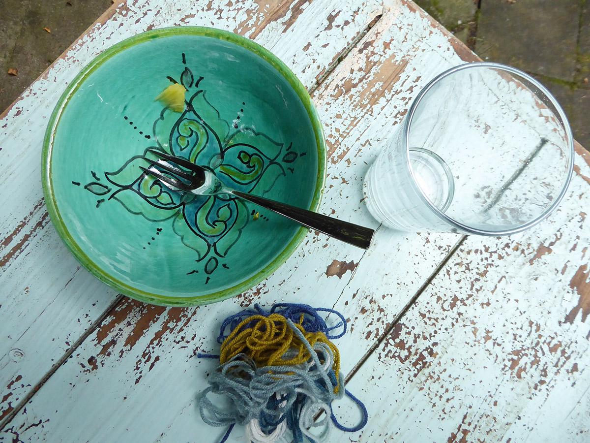 Ein Bild von oben zeigt eine bemalte Schale mit einer Gabel darin, ein Wasserglas und Garnreste auf einer türkisfarbenen Tischplatte