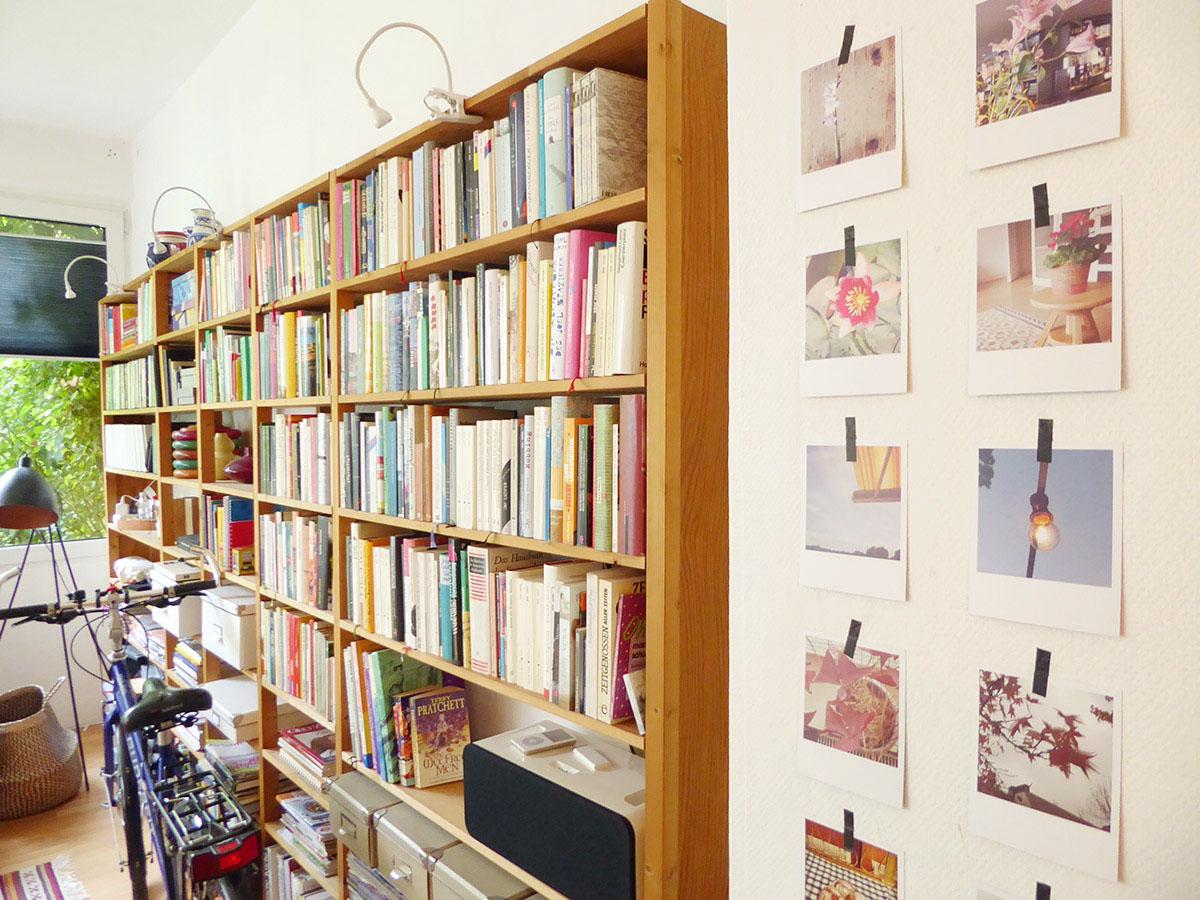 Ein Bücherregal bestückt mit Büchern an der Wand davor eine kleine Galerie aus Polaroids/Origrami-Prints