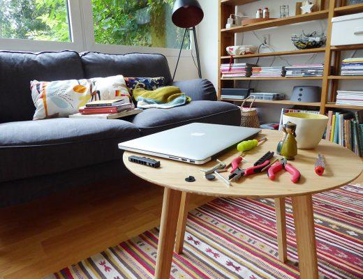 Ein Sofa und davor ein Sofatisch mit einem Laptop und Werkzeug darauf
