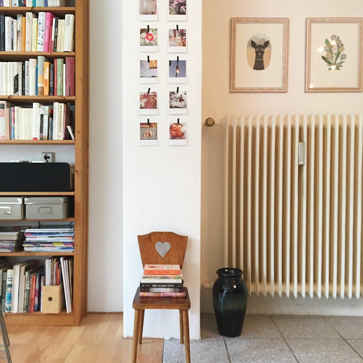 Ausschnitt einer Wohnung mit Bücherregal links, Polaroid-Galerie und Kinderstuhl mit ausgesägtem Herz darunter, rechts Kunstdrucke an der Wand