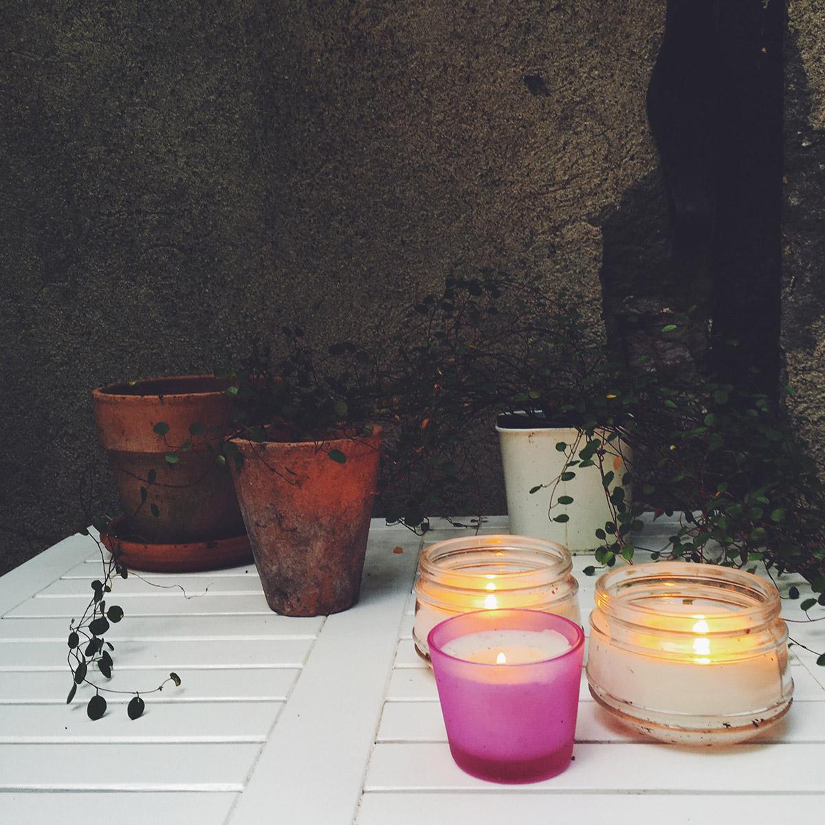 Ein Stilleben aus verschiedenen Blumentöpfen, Pflanzen und Teelichtern in verschiedenen Farben