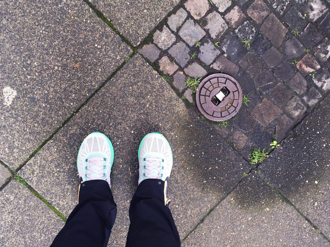 Blick von oben auf Füße in Joggingschuhen, Untergrund ist ein Bürgersteig mit Gehwegplatten