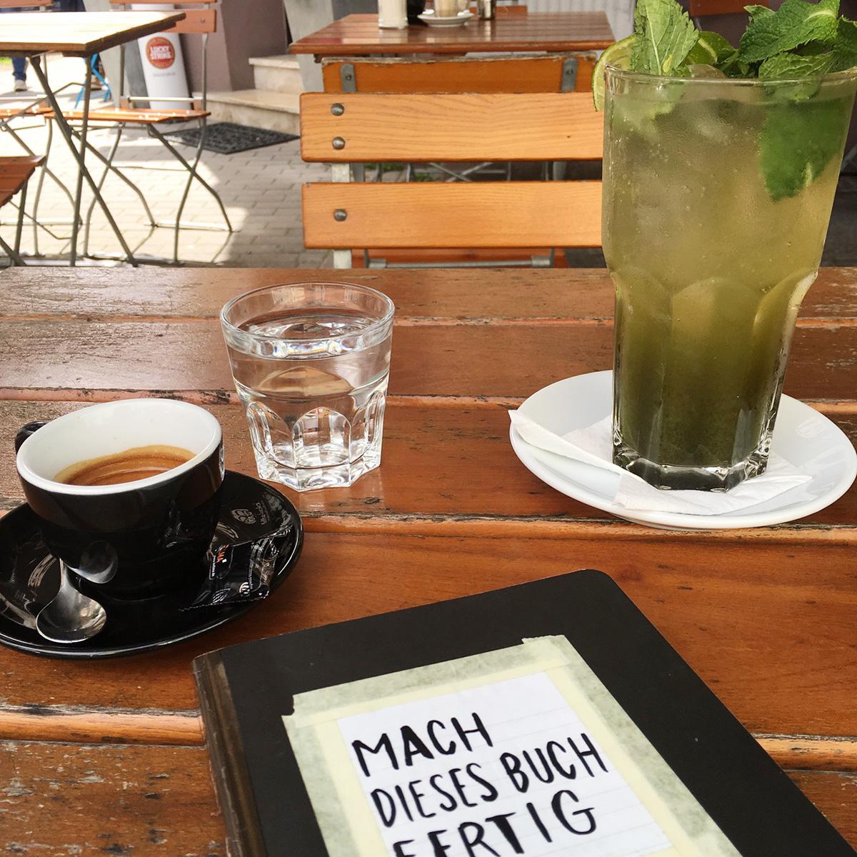 """Ein Espresso, ein kleines Glas Wasser, eine Minzlimonade und das Buch """"Mach dieses Buch fertig"""" auf einem Holztisch"""