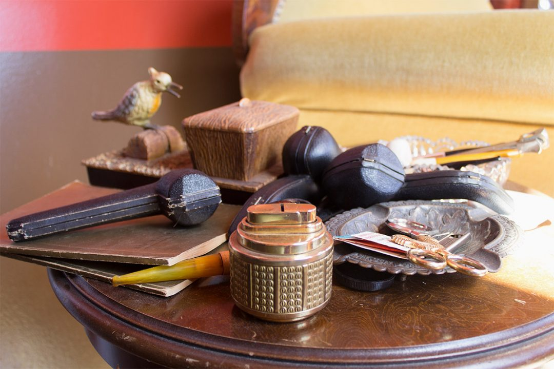 Ein Tisch mit einem Sammelsurium an verschiedenen Pfeifen, Aschenbecher, Feuerzeug, Dosen und Scheren