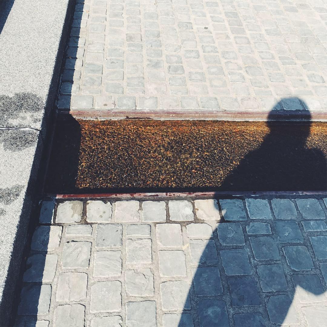 Kopfsteinpflaster mit einer eingelegten Wasserrinne darüber der Schatten einer Frau