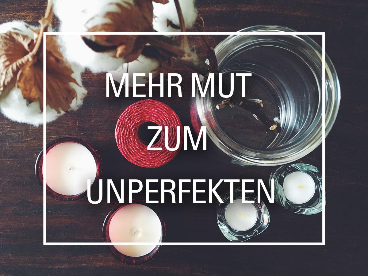 """Stillleben aus verschiedenen Kerzenhaltern, Glasvase mit Baumwollzweig, roter Kordel, davor der Satz """"Mehr Mut zum Unperfekten"""""""