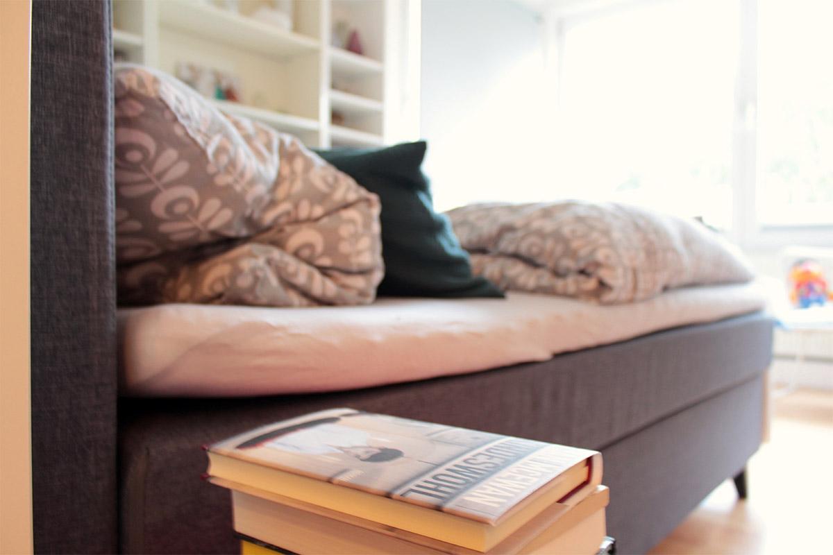 Ein Bücherstapel neben einem Bett