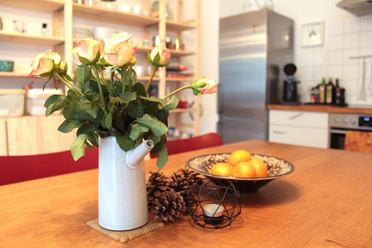 Orangefarbene Rosen in einer grauen Vase, ein Kerzenhalter und Mandarinen in einer Keramikschüssel auf einem Tisch