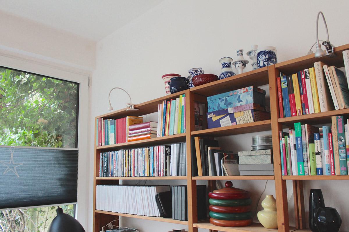 Sammlung von Keramikvasen und Kerzenhaltern auf einem Bücherregal