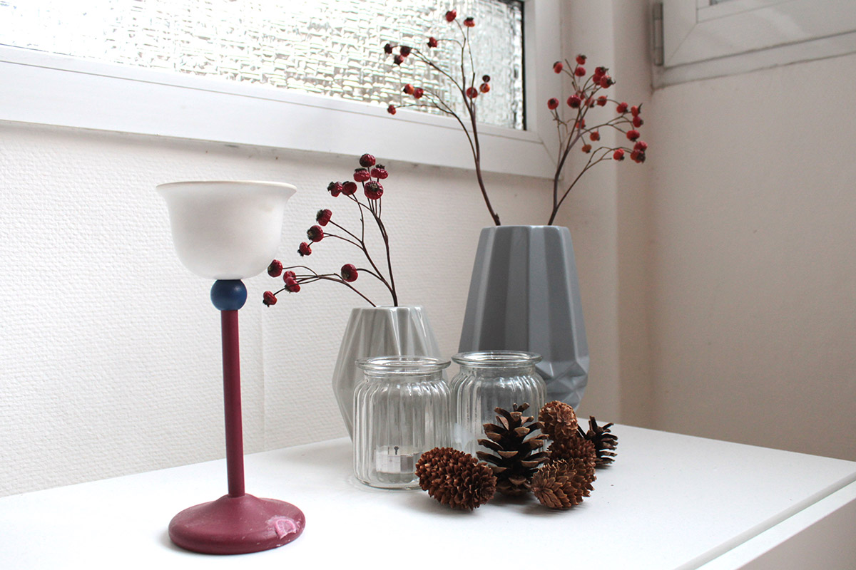 Stilleben aus Vasen, getrockneten Hagebutten, Kerzen und Tannenzapfen