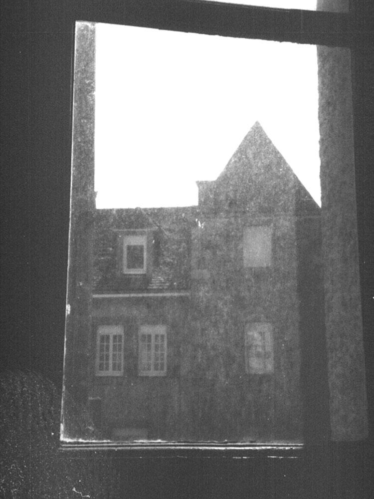 Blick aus einer schmutzigen Fensterscheibe auf ein gegenüberliegendes Haus