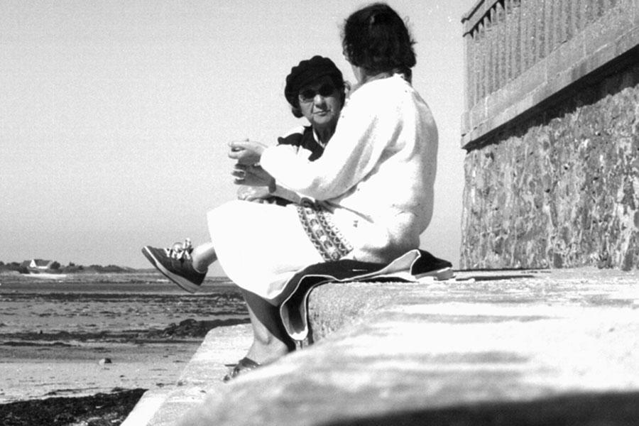 Zwei Frauen sitzen am Strand und unterhalten sich