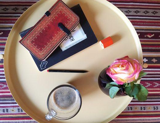 Verschiedene Notizbücher, ein Bleistift, eine Vase mit einer Rose und eine Kaffetasse stehen auf einem Couchtisch