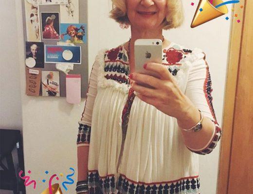 Eine Frau in einer Folklorebluse mit Haarband und Armreifen ist als Hippie für den Karneval verkleidet