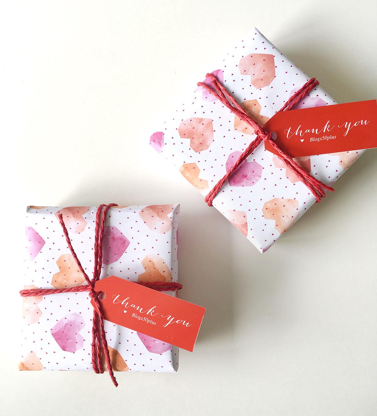 """Zwei Geschenken eingepackt in ein Herz-Geschenkpapier und versehen mit einem Anhänger """"Thank you - Blogs50plus"""" liegen auf einem Tisch"""