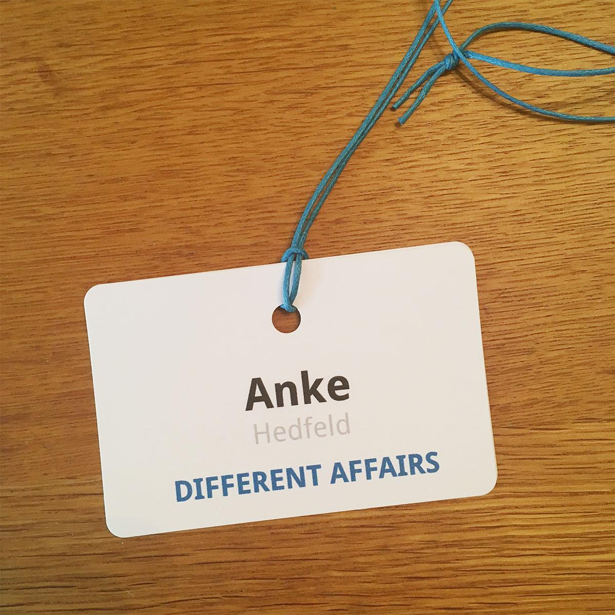 """Ein Namensschild """"Anke Hedfeld - Different Affairs"""" liegt auf einem Tisch"""