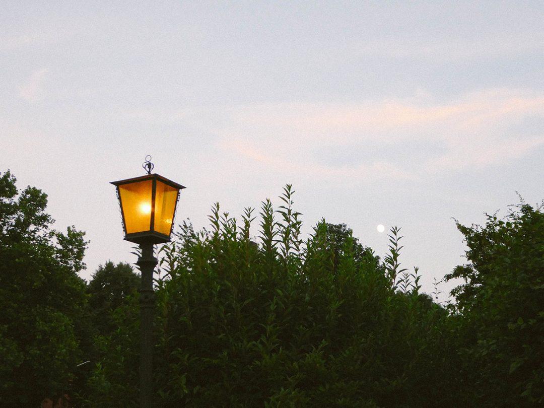 Eine Laterne in einem Garten dahinter der Vollmond