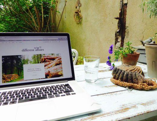 Ein Laptop mit einer aufgerufenen Webseite steht auf einem Gartentisch daneben ein Wasserglas