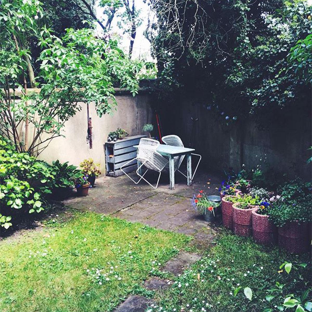 Blick in einen Garten mit Gartenmöbeln und blühenden Pflanzen