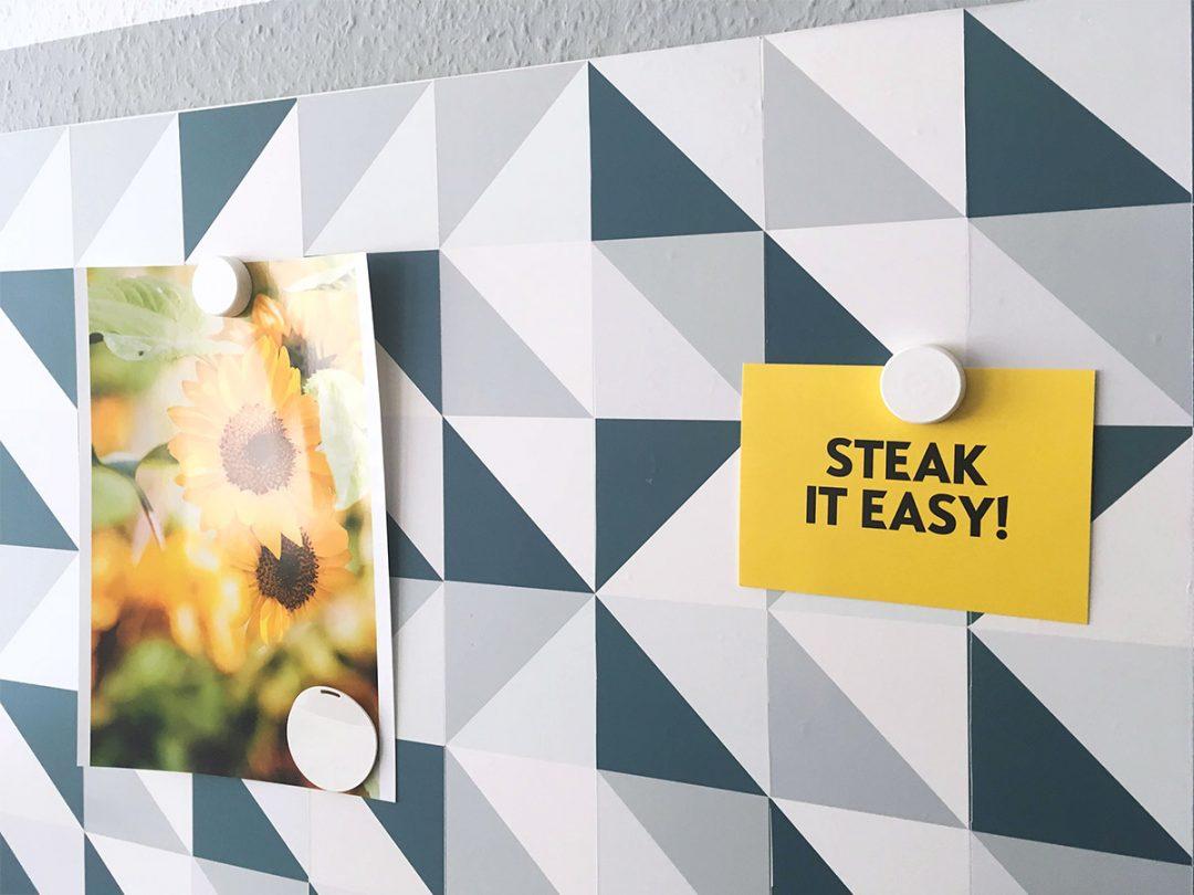 """An einer Pinwand hängt ein Bild mit Sonnenblumen und eine gelbe Postkarte mit dem Aufdruck """"Steak it easy!"""""""