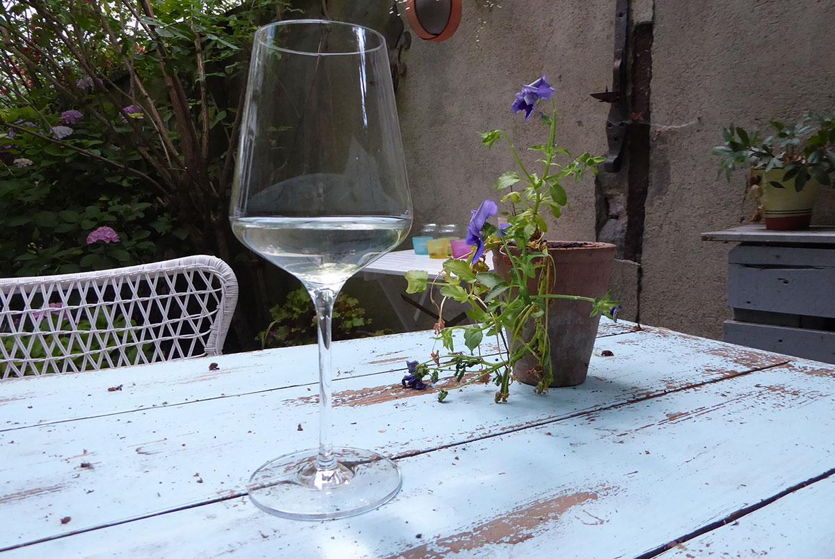 Ein Glas mit Weißwein steht auf einem Gartentisch