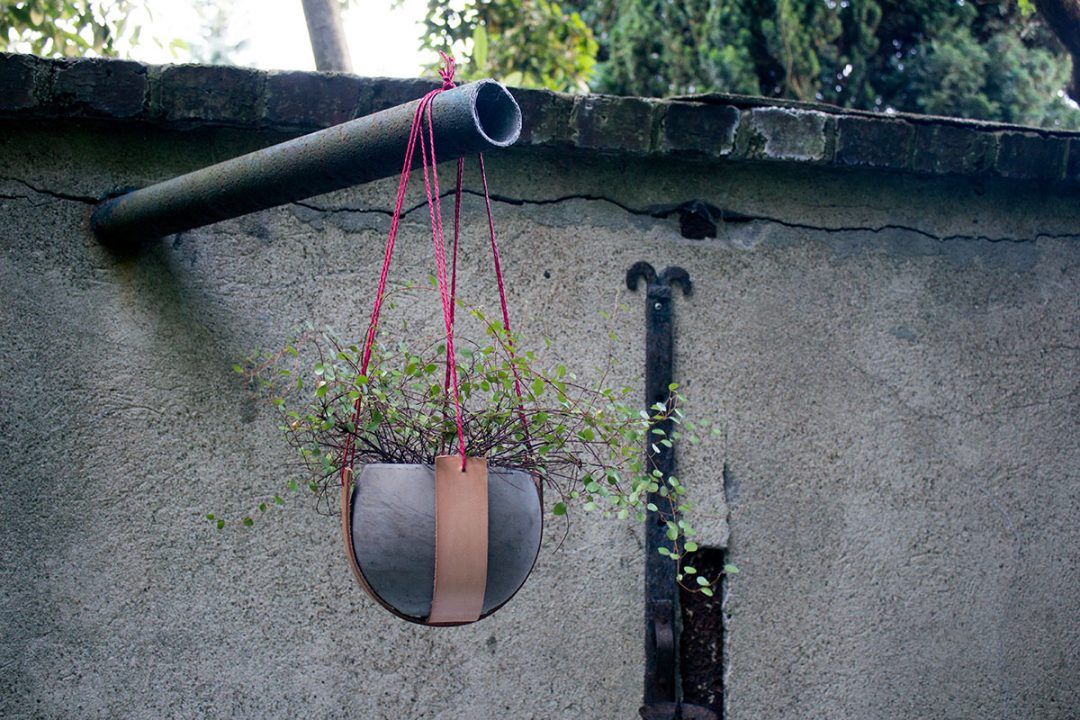 Eine Blumenampel aus Lederstreifen und Paketschnur hängt an einem abgeschnittenen Rohr