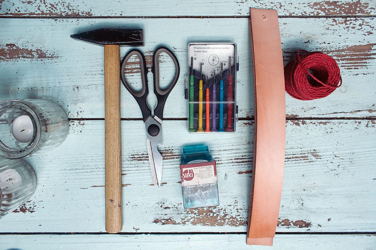 Paketschnur, Lederstreifen, Präzisionswerkzeug, Schere und Hammer liegen auf einem Tisch
